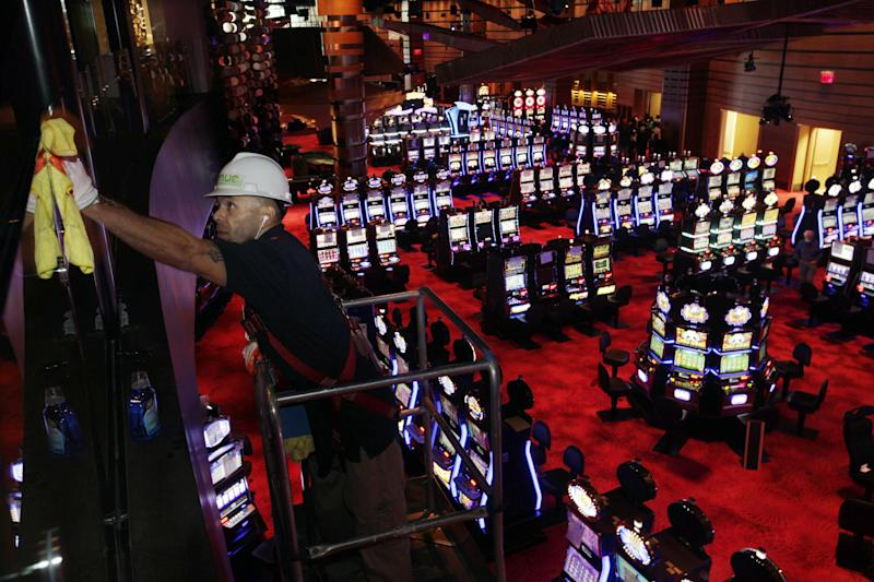 A worker cleans glass above slot machines at Revel in Atlantic City, N.J., Monday, March 19, 2012. Revel, the casino-resort opening April 2, breaks all the old casino rules. The smoke-free resort embraces the ocean rather than turning its back on it. (AP Photo/Mel Evans)