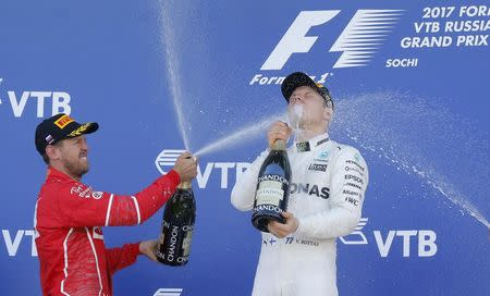 Formula One - F1 - Russian Grand Prix - Sochi, Russia - 30/04/17 - Winner and Mercedes Formula One driver Valtteri Bottas (R) of Finland and second-placed Ferrari Formula One driver Sebastian Vettel of Germany spray champagne on the podium. REUTERS/Maxim Shemetov