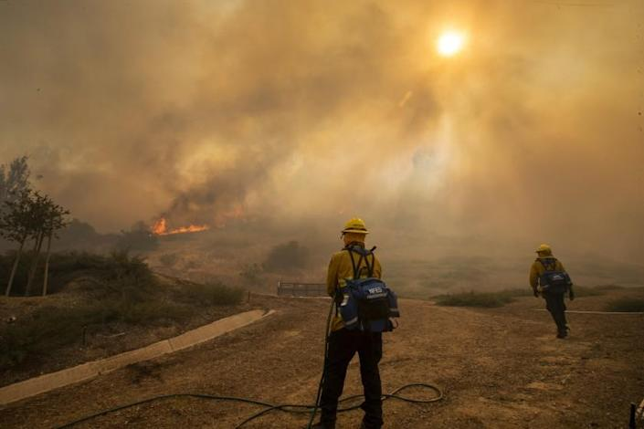 As the Silverado fire approaches the Orchard Hills neighborhood of Irvine Monday, firefighters stand ready to defend homes.