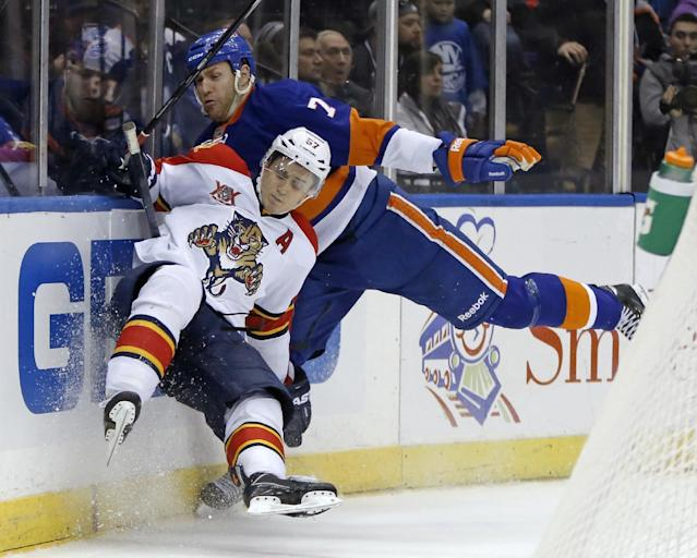 New York Islanders defenseman Matt Carkner (7) checks Florida Panthers center Marcel Goc (57), of Germany, in the third period of an NHL hockey game in Uniondale, N.Y., Sunday, March 2, 2014. The Panthers defeated the Islanders 5-3. (AP Photo/Kathy Willens)