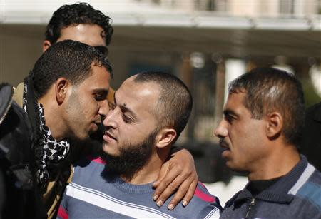 A Palestinian man (C) is hugged by a relative after he was freed from a Hamas-run jail in Gaza City January 8, 2014. REUTERS/Suhaib Salem