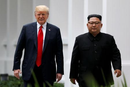 FILE PHOTO: U.S. President Donald Trump and North Korean leader Kim Jong Un walk after lunch at the Capella Hotel on Sentosa island in Singapore