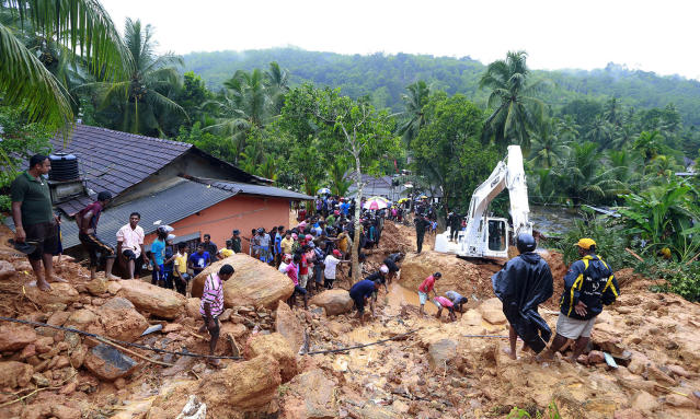 <p>Sri Lankans watch military rescue efforts at the site of a landslide at Bellana village in Kalutara district, Sri Lanka, May 26, 2017. Mudslides and floods triggered by heavy rains in Sri Lanka killed dozens and left many more missing on Friday. (Photo: Eranga Jayawardena/AP) </p>