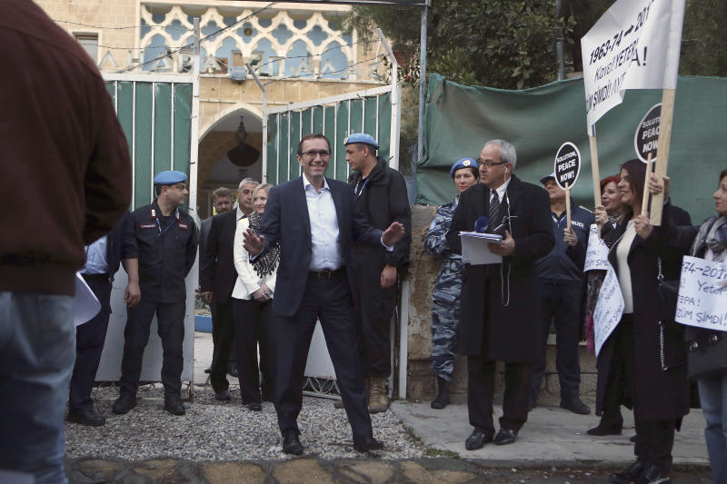 U.N. Special Advisor of the Secretary-General Espen Barth Eide, center, addresses protesters outside the main gate of Ledras Palace, where a dinner for ethnically divided Cyprus' rival leaders will be held, inside the U.N buffer zone in the divided capital Nicosia, Cyprus, Sunday, April 2, 2017. A United Nations-hosted dinner for the two leaders aims to clinch a swift restart of talks that broke down in February amid a squabble over Cyprus' troubled history. (AP Photo/Petros Karadjias)