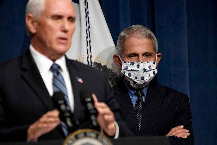 Dr. Anthony Fauci, right, director of the National Institute of Allergy and Infectious Diseases, listens as Vice President Mike Pence speaks during a news conference with the Coronavirus task force at the Department of Health and Human Services in Washington, Friday, June 26, 2020.
