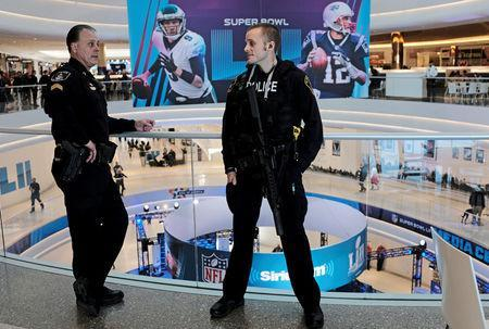 FILE PHOTO: Policemen talk as a Super Bowl promotional banner showing Philadelphia Eagles quarterback Nick Foles and New England Patriots quarterback Tom Brady hangs in an atrium at the Mall of America in Minneapolis, Minnesota, U.S. January 29, 2018 REUTERS/Kevin Lamarque/File Photo