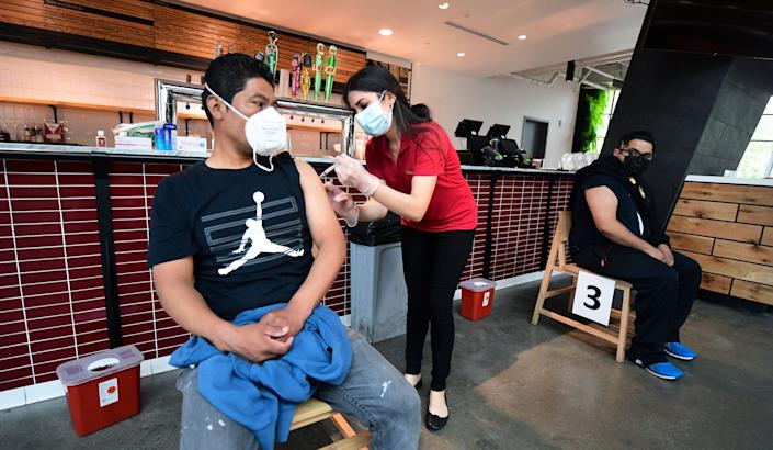 Jose Rodriguez receives his  Johnson & Johnson Covid19 vaccine administered by pharmacist Michelle Hormozia  on May 7, 2021 in Los Angeles, California, at a vaccination clinic setup by Los Angeles Football Club, partnering with the LA county Department of Public Health and USC Pharmacy, where those vaccinated were due to receive a 20% discount on merchandise at the LAFC team store. (Frederic J. Brown/AFP via Getty Images)
