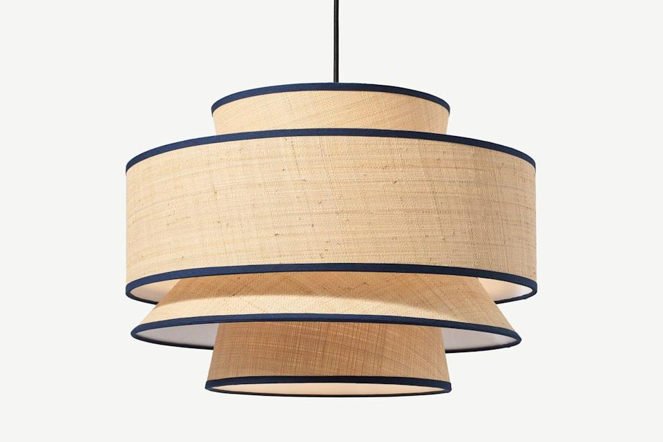 """<p>An interesting mix of classic and contemporary – Made.com marries traditional lampshade shapes all in one design, adding a natural raffia body and slick navy blue ribboning to boot. This piece has a matching table lamp for coordinated decorating. </p><p><strong>Shop now: <a href=""""https://www.made.com/haroon-layered-lamp-shade-natural-raffia"""" rel=""""nofollow noopener"""" target=""""_blank"""" data-ylk=""""slk:Haroon Layered Lamp Shade in Raffia at Made.com"""" class=""""link rapid-noclick-resp"""">Haroon Layered Lamp Shade in Raffia at Made.com</a></strong></p>"""