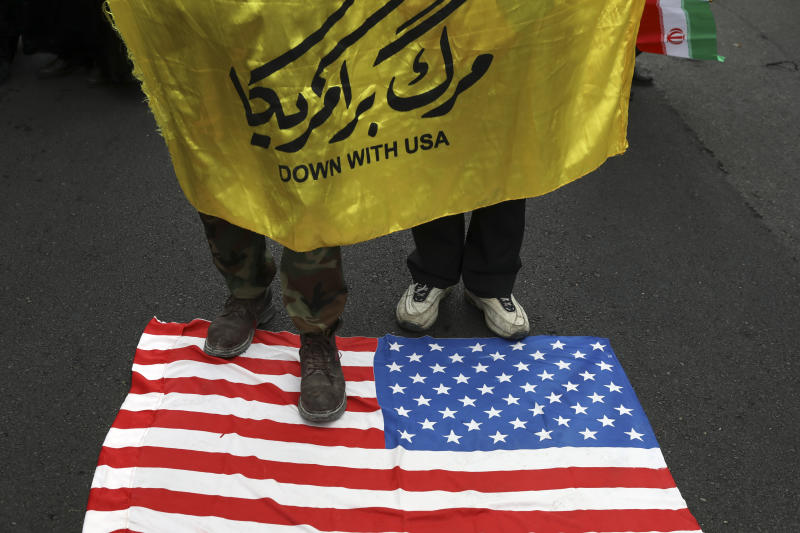 """Demonstrators hold an anti-U.S. banner as they stand on a makeshift U.S. flag during an annual rally in front of the former U.S. Embassy in Tehran, Iran, Monday, Nov. 4, 2019. Reviving decades-old cries of """"Death to America,"""" Iran on Monday marked the 40th anniversary of the 1979 student takeover of the U.S. Embassy in Tehran and the 444-day hostage crisis that followed as tensions remain high over the country's collapsing nuclear deal with world powers. (AP Photo/Vahid Salemi)"""