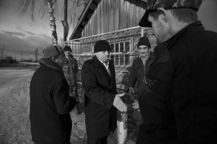 In this Nov. 14, 2012, photo, Eduard Mochalov, center, greets former employees of his agricultural concern in Yarabaikasy near Cheboksary, the capital city of Chuvashia, Russia. Mochalov has found a new lease on life as a crusading journalist investigating corruption in his native region, fueled by tips from disgruntled businessmen and government workers. Undeterred by a system where the law is selectively used to protect the powerful and crack down on critics, Mochalov has quickly earned cult status _ not to mention the ire of countless local officials _ throughout the small province of Chuvashia. (AP Photo/Alexander Zemlianichenko)