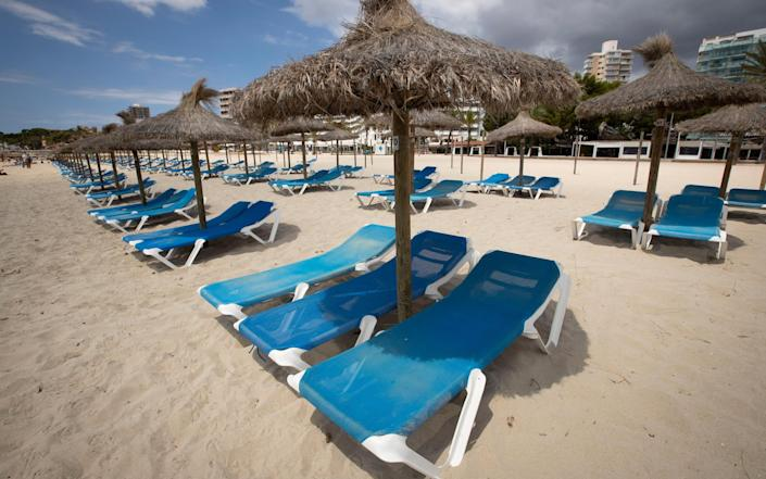 Empty deck chairs at Magaluf beach in Majorca - GETTY