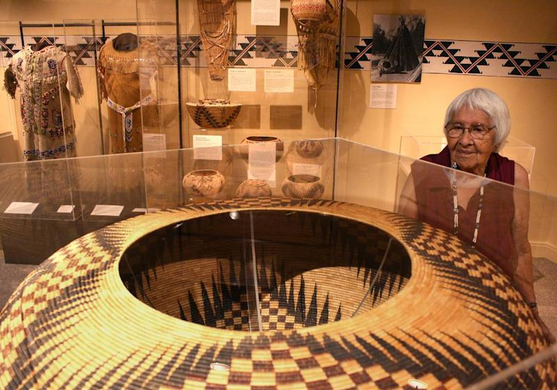 In this 2014 photo, Helen Coats, who is Miwuk and Paiute, looks at a large basket made by her grandmother Lucy Telles on display in the Indian Cultural Museum in Yosemite Valley. In the background are an array of smaller traditional baskets, cradleboards and clothes also made by Telles.