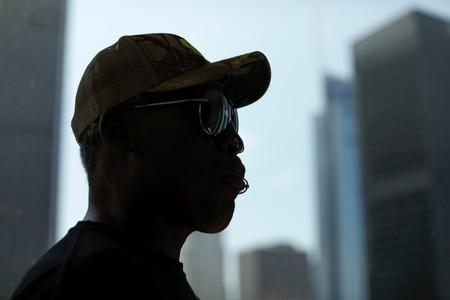 Former NBA player Dennis Rodman is silhouette next to the skyline of Los Angeles as he poses for a portrait in Los Angeles, California