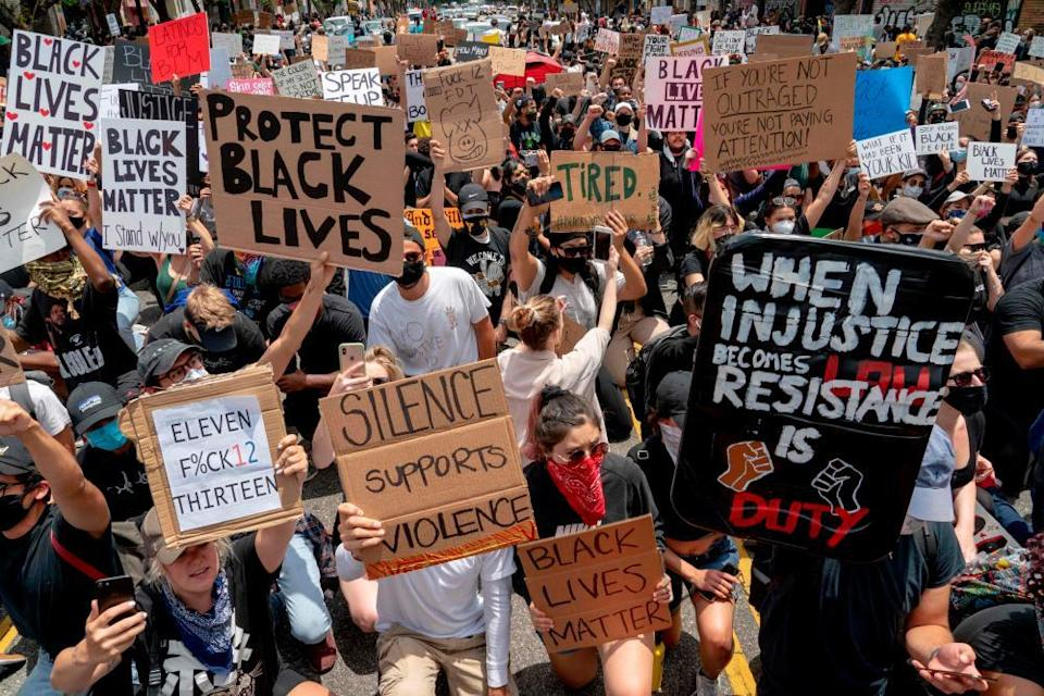 Protesters kneel in front of the police during a demonstration over the death of George Floyd in Los Angeles on 2 June 2020.