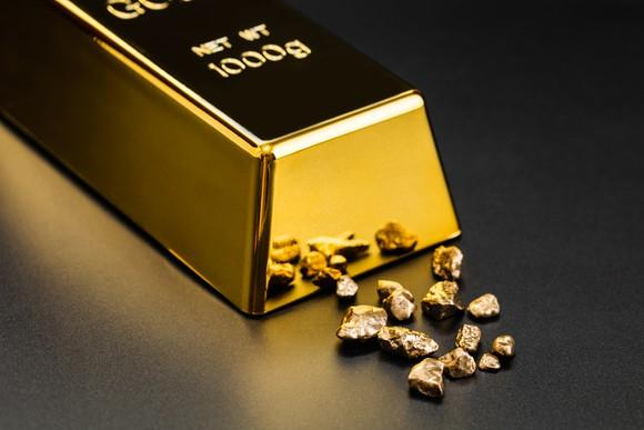 A polished bar of gold bullion next to smaller gold fragments.