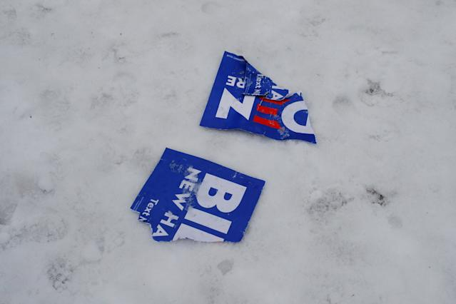 A torn Biden campaign sign in the snow outside a polling site in Manchester on Feb. 11. (Brian Snyder/Reuters)