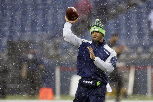 Seattle Seahawks quarterback Russell Wilson warms up in the rain before an NFC divisional playoff NFL football game against the New Orleans Saints in Seattle, Saturday, Jan. 11, 2014. (AP Photo/Ted S. Warren)