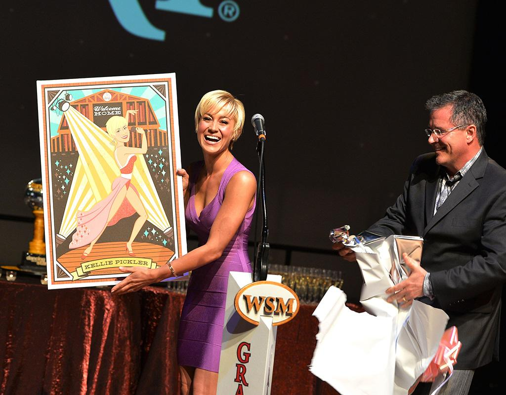 "Kellie Pickler was presented with her spitting image when she attended a homecoming in her honor at the Grand Ole Opry in her hometown of Nashville. Guess they were really impressed with her ""Dancing With the Stars"" win! (6/4/2013)"