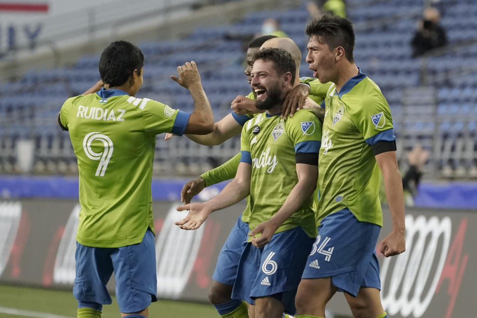 Seattle Sounders midfielder Joao Paulo (6) celebrates with forward Raul Ruidiaz (9) and midfielder Josh Atencio, right, after Paulo scored a goal against Minnesota United during the second half of an MLS soccer match, Friday, April 16, 2021, in Seattle. (AP Photo/Ted S. Warren)