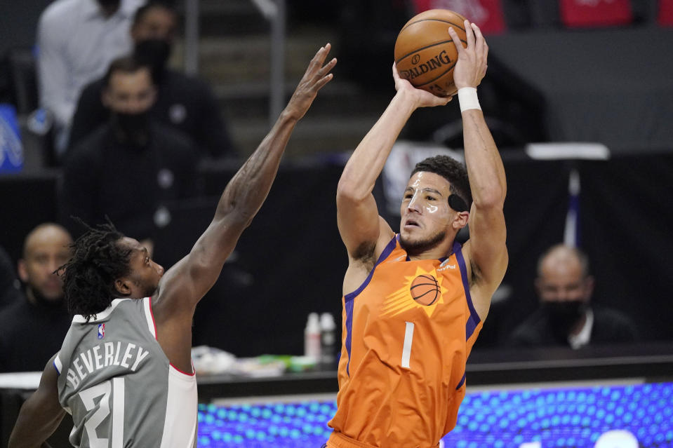 Phoenix Suns guard Devin Booker, right, shoots as Los Angeles Clippers guard Patrick Beverley defends during the first half in Game 4 of the NBA basketball Western Conference Finals Saturday, June 26, 2021, in Los Angeles. (AP Photo/Mark J. Terrill)