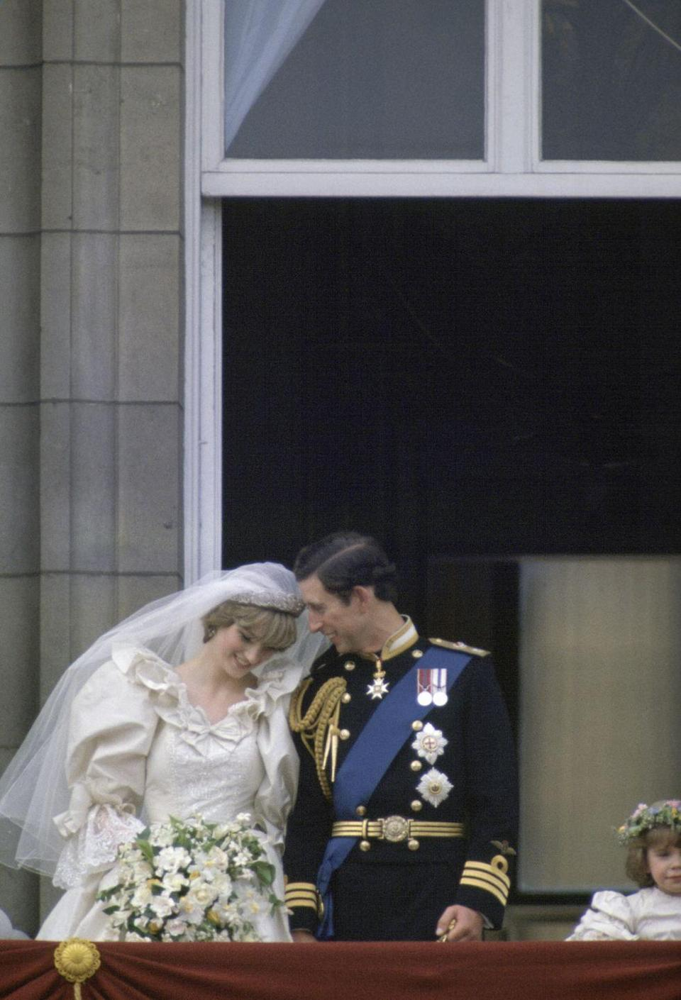 <p>Charles and Diana appear rather bashful on the balcony, where it's customary to share a kiss. </p>