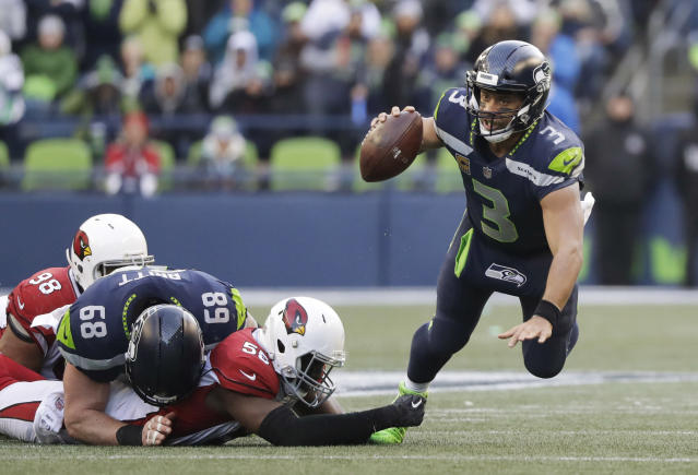 <p>Seattle Seahawks quarterback Russell Wilson, right, is tripped by Arizona Cardinals outside linebacker Chandler Jones, second from right, in the second half of an NFL football game, Sunday, Dec. 31, 2017, in Seattle. (AP Photo/Elaine Thompson) </p>