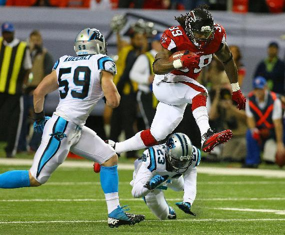Atlanta Falcons running back Steven Jackson leaps over Carolina Panthers cornerback Melvin White for a first down in the first half of an NFL football game Sunday, Dec. 29, 2013, in Atlanta. (AP Photo/Atlanta Journal-Constitution, Curtis Compton)
