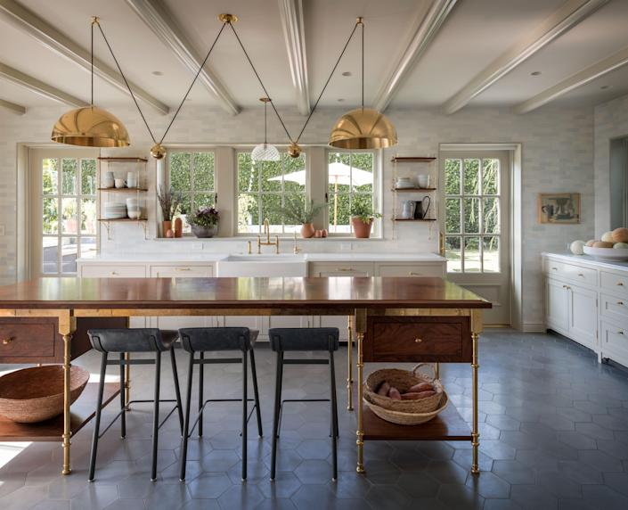 In the primary kitchen area, pendant light fixtures steal the show. Above the island, an extra-large Florian Schulz double posa lamp hangs, while a piece custom-fabricated by Andrew Scott Paiko can be seen above the farm sink. The woodwork and metalwork were both done by Earthbound Industries.