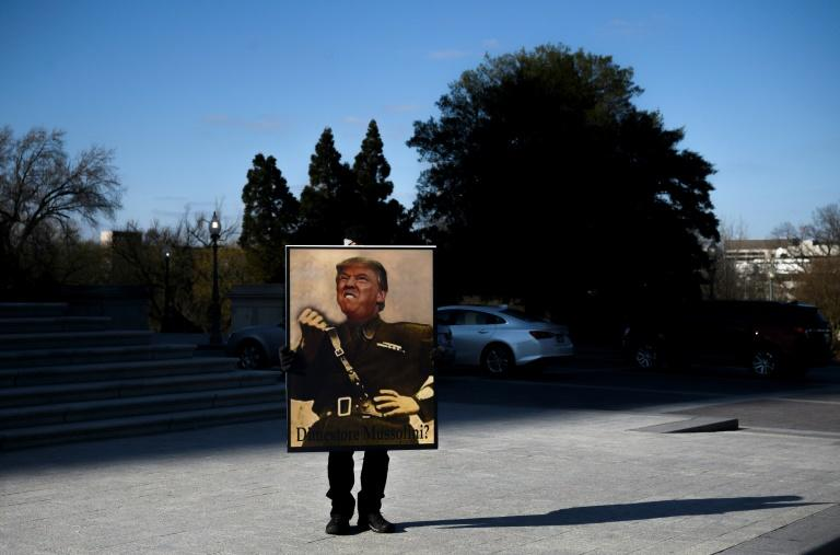 An opponent of President Donald Trump near the US Capitol where he was on trial in the Senate after being impeached in the House of Representatives (AFP Photo/Andrew CABALLERO-REYNOLDS)