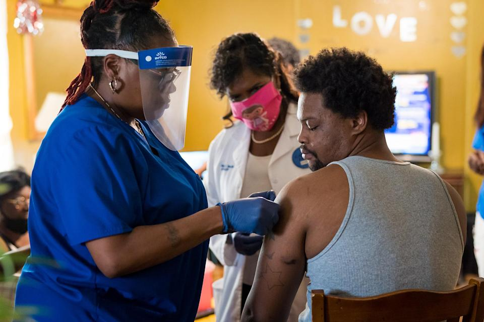 Keshawn Shaw looks at his arm where nurse Andretta Griffin, left, and Dr. Karen Smith, center, administered a Covid-19 vaccination at his grandmother Bessie Bratcher's home in Raeford, N.C. (Justin Kase Conder / for NBC News)
