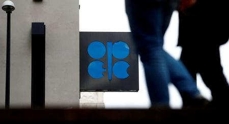 FILE PHOTO: People walk past the logo of the Organization of the Petroleum Exporting Countries (OPEC) in front of its headquarters in Vienna, Austria September 21, 2017.   REUTERS/Leonhard Foeger/File Photo