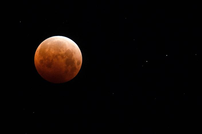 """A full moon is seen during totality of a total lunar eclipse as the moon enters Earth's shadow for a """"Super Blood Moon"""" on May 26, 2021 in Chico, Calif."""