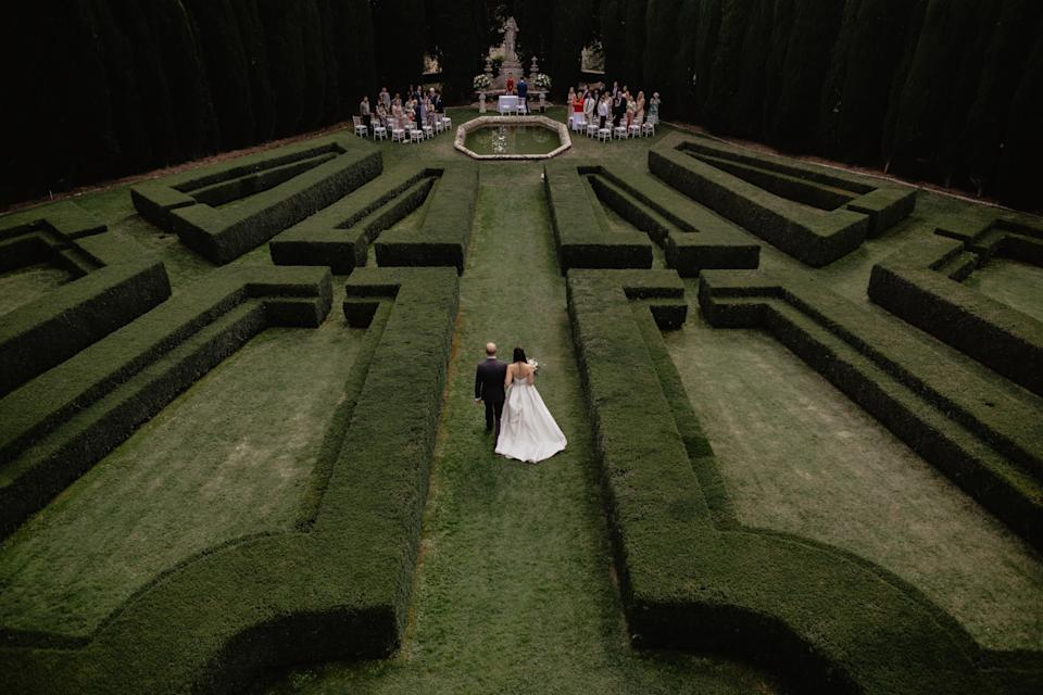 <p>Bride and groom walk through the aisle in the middle of a maze to meet wedding guests at the end. <em>[Photo: FEDERICA CAVICCHI / JUNEBUG WEDDINGS / CATERS]</em> </p>