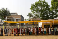Voters stand in a queue to cast their votes outside a polling booth during first phase of elections in West Bengal state in Medinipur, India, Saturday, March 27, 2021. Voting began Saturday in two key Indian states with sizeable minority Muslim populations posing a tough test for Prime Minister Narendra Modi's popularity amid a months-long farmers' protest and the economy plunging with millions of people losing jobs because of the coronavirus pandemic. (AP Photo/Bikas Das)