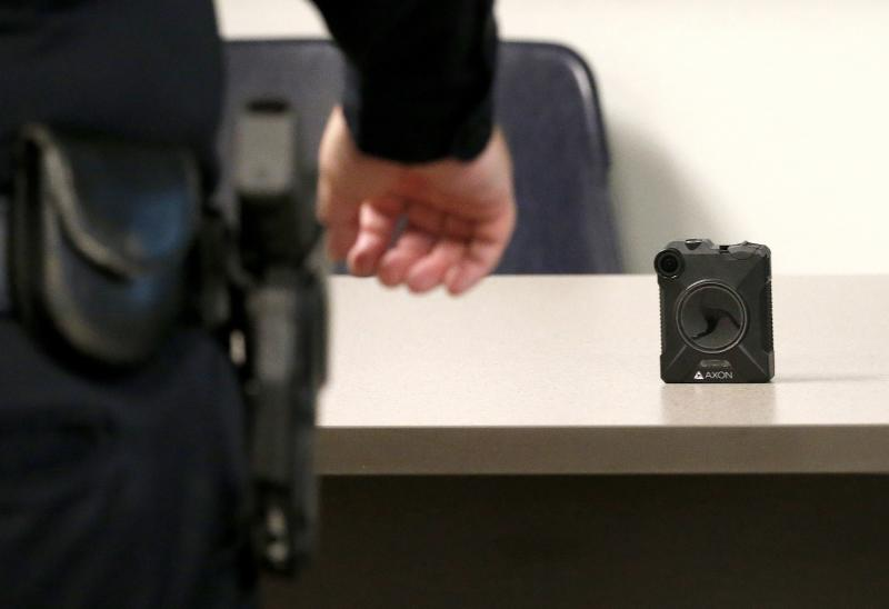 Phoenix Police Department officer reaches for his the new Axon Body 2 body camera as another precinct gets their cameras assigned to them Wednesday, July 3, 2019, in Phoenix. Although body-worn cameras are becoming a police standard nationwide, Phoenix was among the last big departments to adopt their widespread use. (AP Photo/Ross D. Franklin)