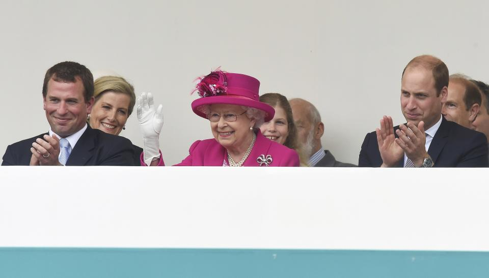 Peter Phillips (L) and Prince William, Duke of Cambridge (R) look on as Queen Elizabeth II waves to guests attending