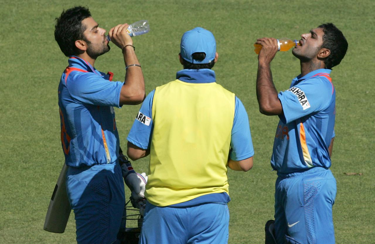 Indian captain Virat Kohli (L) and Ambabti Rayudu (R) drink water during the first match of the five match ODI cricket series between India and hosts Zimbabwe at the Harare Sports Club on July 24 2013. AFP PHOTO /Jekesai Njikizana.        (Photo credit should read JEKESAI NJIKIZANA/AFP/Getty Images)