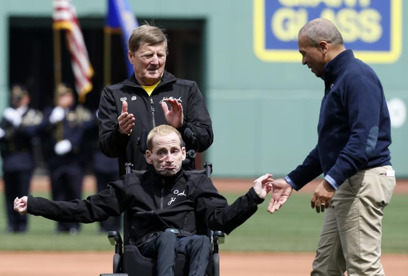 Massachusetts Gov. Deval Patrick, right, greets marathoners Rick Hoyt, bottom, and his father Dick before the ceremonial first pitch in a baseball game between the Boston Red Sox and the Kansas City Royals in Boston, Saturday, April 20, 2013. (AP Photo/Michael Dwyer)