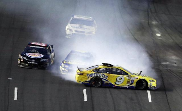 Marcos Ambrose (9) spins as AJ Allmendinger is engulfed in smoke during the NASCAR Sprint Cup series Coca-Cola 600 auto race at the Charlotte Motor Speedway in Concord, N.C., Sunday, May 25, 2014. Ryan Truex avoids the collision at left. (AP Photo/Gerry Broome)