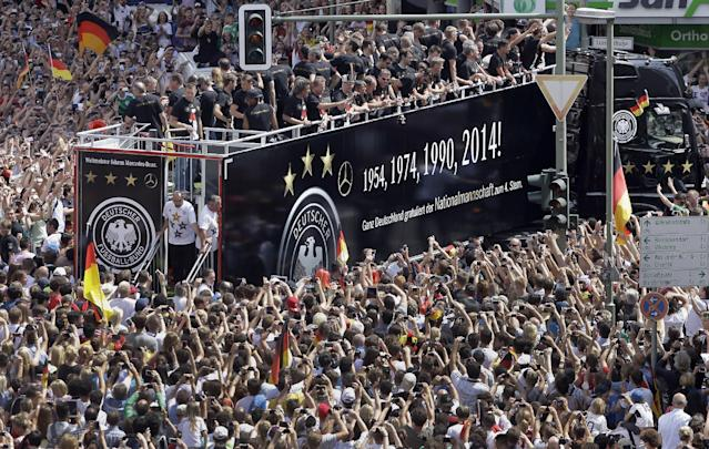 "Members of the German soccer squad wave to fans after the arrival of the German national soccer team in Berlin Tuesday, July 15, 2014. Germany's World Cup-winning team has returned home from Brazil to celebrate the country's fourth title with huge crowds of fans. The team's Boeing 747 touched down at Berlin's Tegel airport midmorning Tuesday after flying a lap of honor over the ""fan mile"" in front of the landmark Brandenburg Gate. (AP Photo/Michael Sohn)"