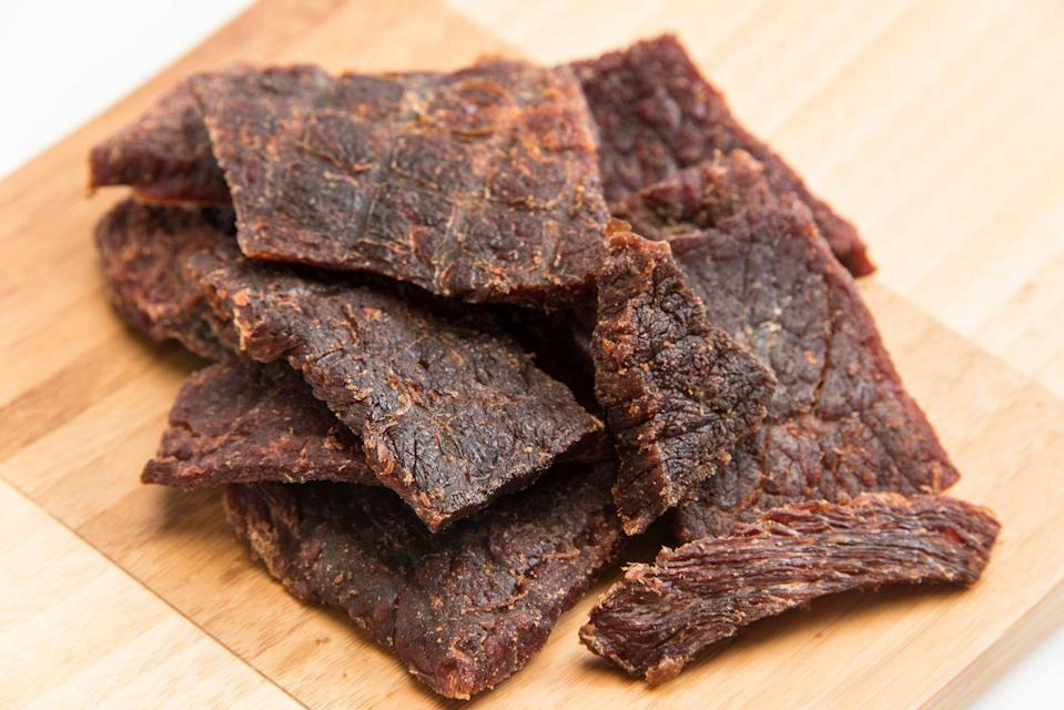 "<p>Biltong is a dried, cured meat served as strips. ""The <a href=""https://urldefense.com/v3/__http:/www.eatbiltong.com/__;!SxXtNzbPoJo!wRGZNnOmjTsiKo52FoCrWV30hXUNtc_SjmXi3aVXmfeR65uC1tDHz5knoKkziLrZZ8Q$"" rel=""nofollow noopener"" target=""_blank"" data-ylk=""slk:Kalahari"" class=""link rapid-noclick-resp"">Kalahari</a> version in particular is a simple snack that packs in 32 grams of protein and 160 calories, making it an excellent addition to a weight loss diet,"" says <a href=""https://draxe.com/"" rel=""nofollow noopener"" target=""_blank"" data-ylk=""slk:Josh Axe"" class=""link rapid-noclick-resp"">Josh Axe</a>, D.C., D.N.M., C.N.S., clinical nutritionist and author of several books including <em><a href=""https://www.amazon.com/Eat-Dirt-Health-Problems-Surprising/dp/0062433679/?tag=syn-yahoo-20&ascsubtag=%5Bartid%7C10050.g.35715141%5Bsrc%7Cyahoo-us"" rel=""nofollow noopener"" target=""_blank"" data-ylk=""slk:Eat Dirt"" class=""link rapid-noclick-resp"">Eat Dirt</a></em>. ""Protein works to lower levels of ghrelin, the hormone responsible for stimulating hunger, to help curb cravings and increase weight loss.""</p>"