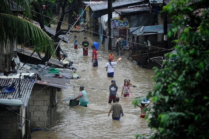 Residents wade through a flooded street in San Mateo, Rizal province on August 13 (AFP Photo/Noel Celis)