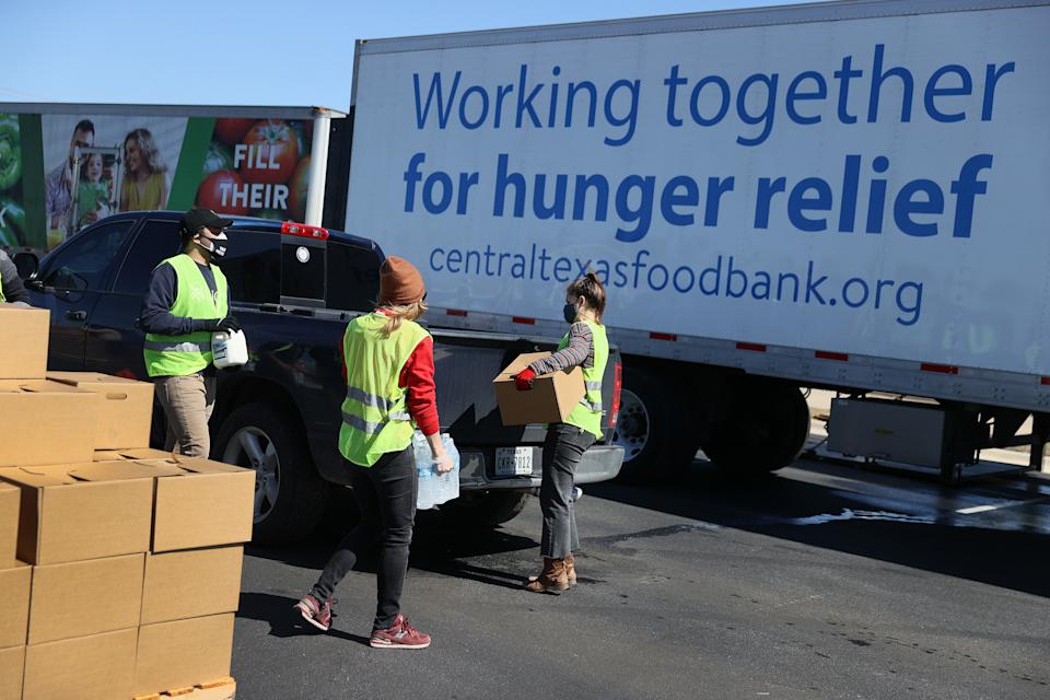 Volunteers with the Central Texas Food Bank give food to those in need at a drive thru distribution point setup at Del Valle High School on February 20, 2021 in Austin, Texas.  (Photo by Joe Raedle/Getty Images)