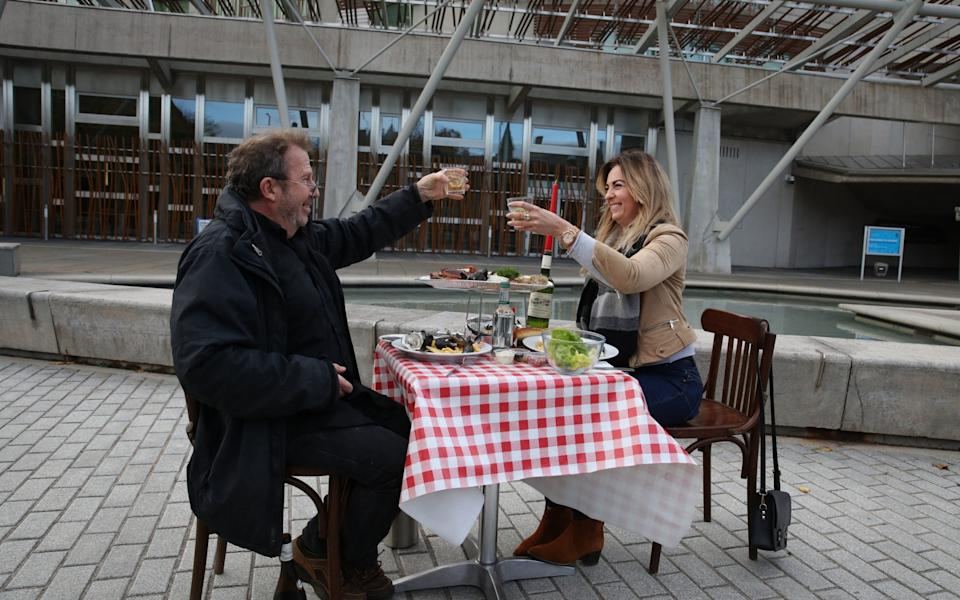 Pierre Levicky owner of Chez Jules restaurant in Edinburgh alongside Kasia Panisco as they stage a protest by having a meal outside the Scottish Parliament in Edinburgh after a range of new restrictions to combat the rise in coronavirus cases came into place in Scotland - PA