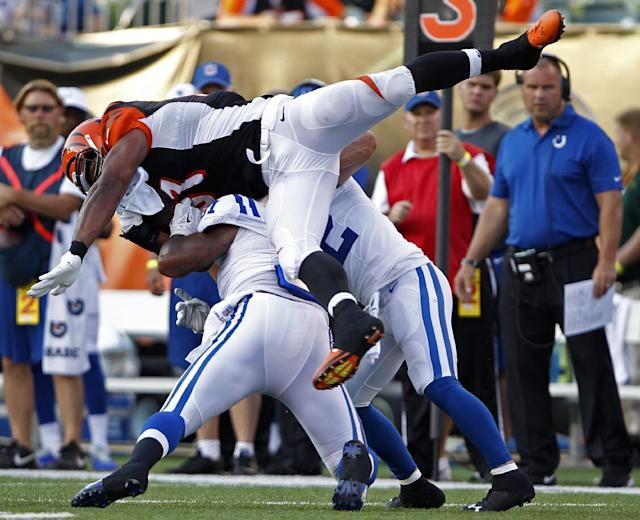Cincinnati Bengals tight end Alex Smith, top, is tackled by Indianapolis Colts defensive end Jonathan Newsome and free safety Colt Anderson, right, in the first half of an NFL preseason football game, Thursday, Aug. 28, 2014, in Cincinnati. (AP Photo/Frank Victores)