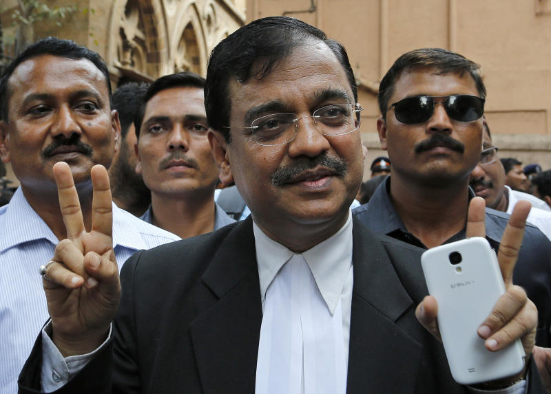 Public Prosecutor Ujjwal Nikam displays the victory symbol as he comes out of a court in Mumbai, India, Friday, April 4, 2014. The Indian court on Friday sentenced to death three men who raped a photojournalist inside an abandoned textile mill in the financial hub of Mumbai last year. A fourth defendant was sentenced to life in prison, Nikam said. (AP Photo/Rajanish Kakade)