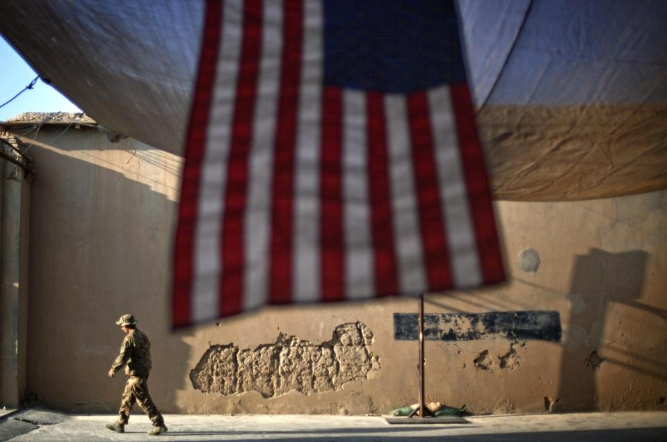 FILE - In this Sept. 11, 2011 file photo, a U.S. Army soldier walks past an American Flag hanging in preparation for a ceremony commemorating the tenth anniversary of the 9/11 attacks, at Forward Operating Base Bostick in Kunar province, Afghanistan. After 20 years of military engagement and billions of dollars spent, NATO and the United States still grapple with the same, seemingly intractable conundrum — how to withdraw troops from Afghanistan without abandoning the country to even more mayhem. President Joe Biden is reviewing his predecessor's 2020 deal with the Taliban, which includes a May 1, 2021, deadline for a final U.S. troop withdrawal. (AP Photo/David Goldman, File)