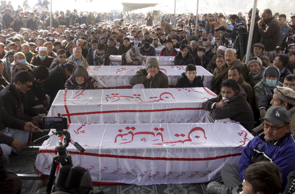 People from the Shiite Hazara community gather around the caskets of coal mine workers who were killed by unknown gunmen near the Machh coal field, during a sit-in protest, in Quetta, Pakistan, Monday, Jan. 4, 2021. Gunmen opened fire on a group of minority Shiite Hazara coal miners after abducting them, killing 11 in southwestern Baluchistan province early Sunday, a Pakistani official said. (AP Photo/Arshad Butt)