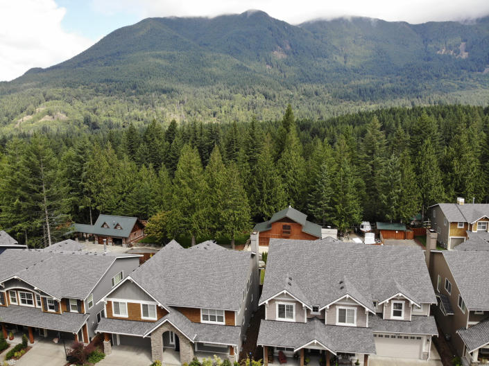 In this photo taken July 24, 2019, houses are backed up to a forest in the Cascade foothills of North Bend, Wash. Experts say global warming is changing the region's seasons, bringing higher temperatures, lower humidity and longer stretches of drought. And that means wildfire risks in coming years will extend into areas that haven't experienced major burns in residents' lifetimes. (AP Photo/Elaine Thompson)