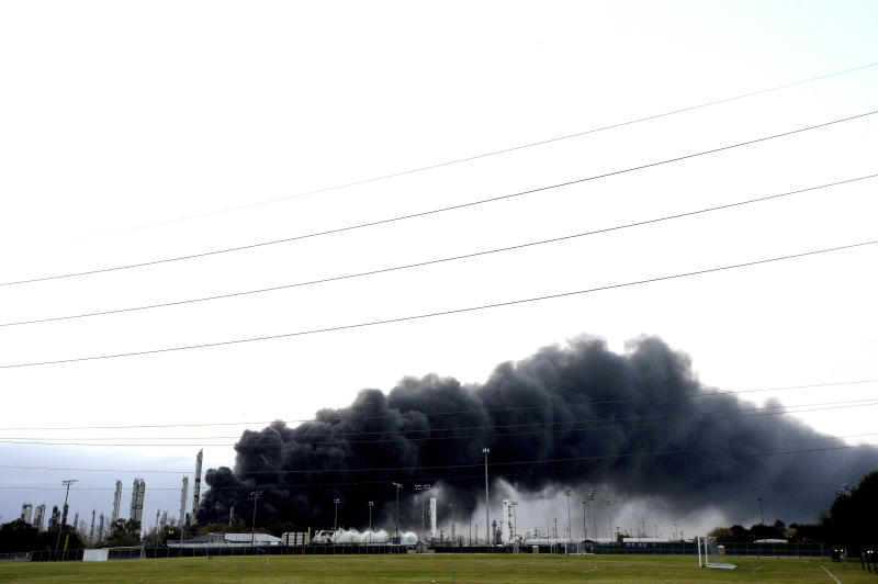 Thick smoke fills the sky above the TPC Group Port Neches Operations as emergency response crews try to contain the fire that continued to burn throughout the morning following an overnight explosion on Wednesday, Nov. 27, 2019, in Port Neches, Texas.  Three workers were injured early Wednesday in a massive explosion at the Texas chemical plant that also blew out the windows and doors of nearby homes. (Kim Brent/The Beaumont Enterprise via AP)
